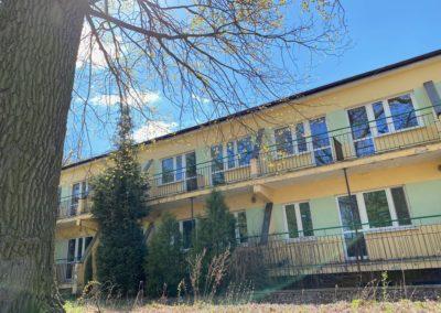 Widać długi jednopiętrowy budynek wczasowy - na parterze i piętrze balkony. Budynek w kolorze żółto - seledynowym (kolory ułożone w pasy). Po lewej stronie na pierwszym planie widać pień drzewa. pień