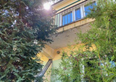 Po lewej i prawej stronie widać zielone tuje. Pośrodku widać budynek. Zdjęcie wykonano od dołu. Widać spód zniszczonego balkonu i okno balkonowe.