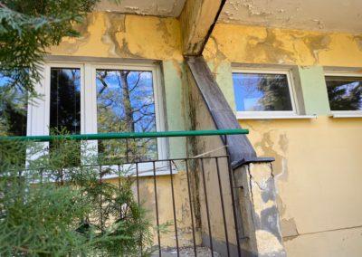 Fragment żółtego budynku - widać kawałek balkonu z lewej strony i małe okienko z prawej. Ściany obdrapane.