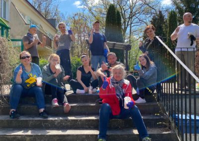 Grupa ok. 10 osób siedzi na zewnątrz na betonowych schodach. Są ubrani na roboczo, szczęśliwi, ale zmęczeni.