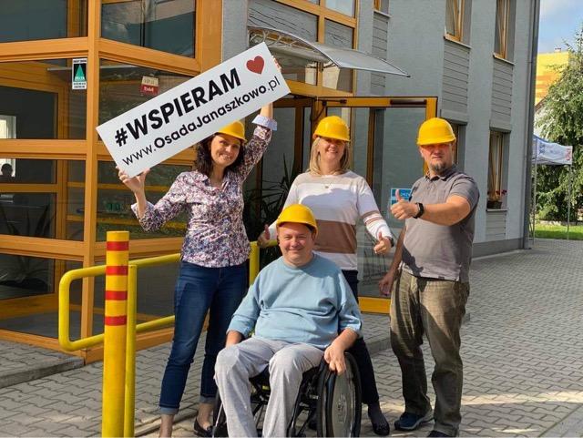 """Na zdjęciu widać cztery osoby w średnim wieku w żółtych kaskach budowlanych. Dwie kobiety i jeden mężczyzna stoją, a przed nimi na wózku inwalidzkim siedzi jeszcze jeden mężczyna. Wszyscy uśmiechnięci, stoją w słońcu przed budynkiem, patrzą w obiektyw. Kobieta z lewej trzyma nad głową planszę z napisem """"Wspieram www.OsadaJanaszkowo.pl"""""""